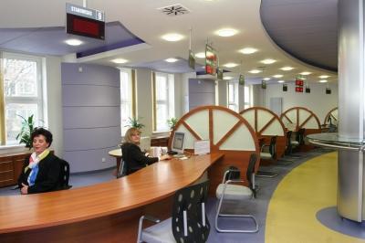 Wnętrze Centrum Obsługi Podatnika. W tle dwie urzędniczki siedzące przy stanowiskach pracy w gotowości do obsługi interesantów.